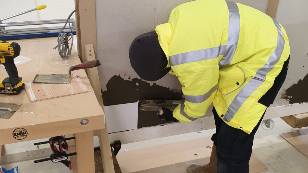 Male construction student tiling a wall