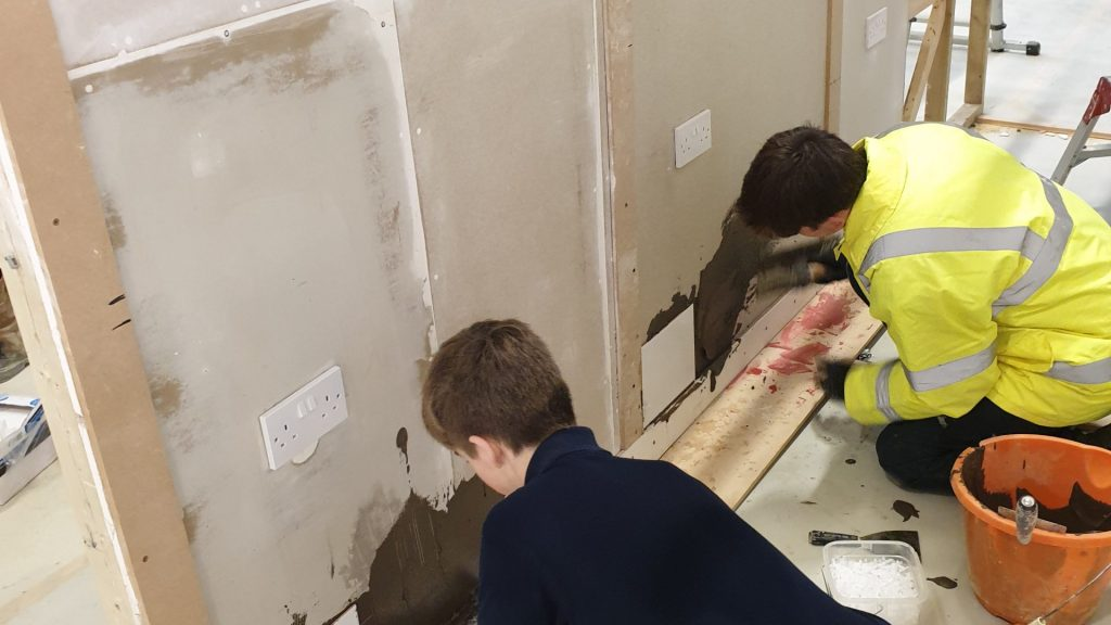 Male construction students tiling a wall