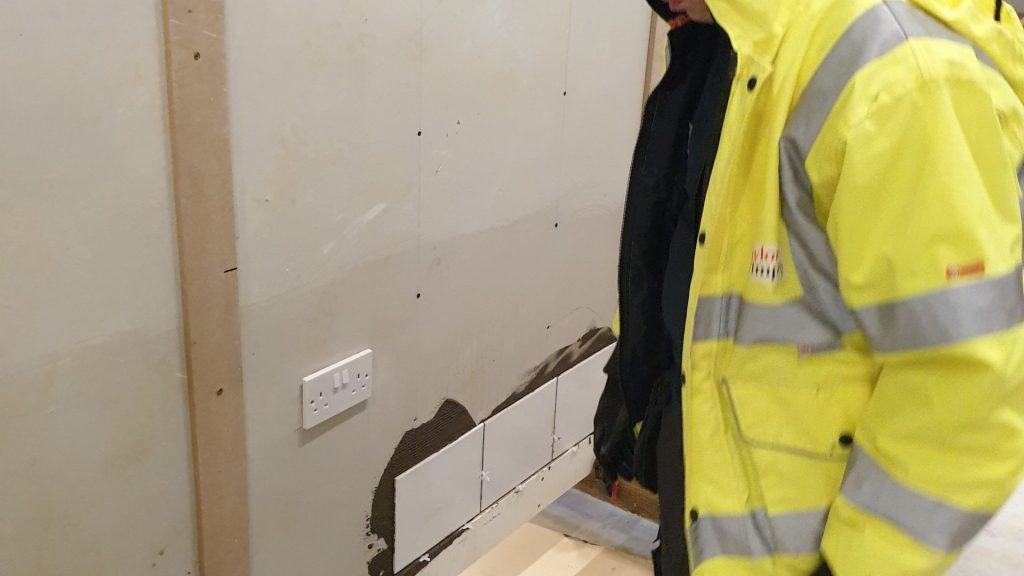 Male construction student tiling a wall close up