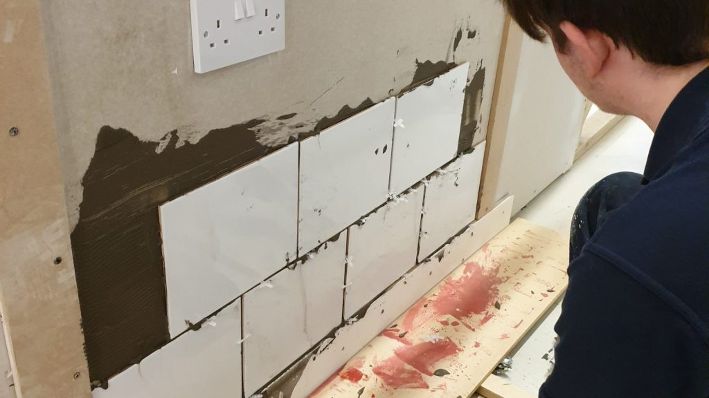 Close up of male construction student admiring tiling work