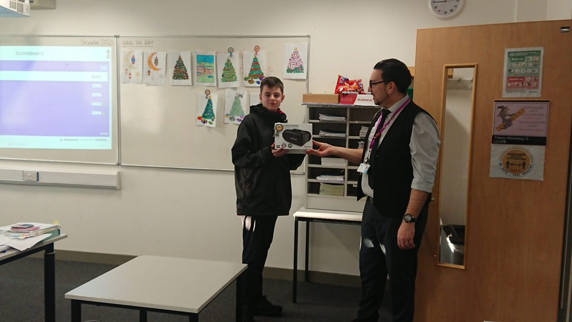 Male student holding VR headset prize